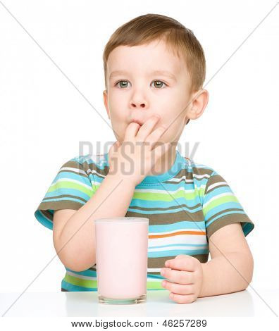 Cute little boy with a glass of milk sucking his finger, isolated over white