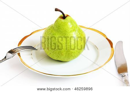 Green Pear On A White Plate