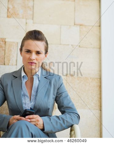 Business Woman With Cell Phone Sitting On Terrace