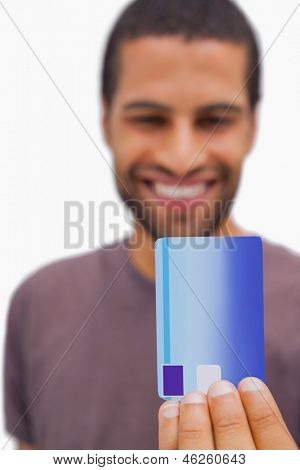 Handsome man holding credit card on white background