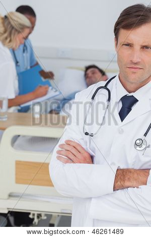 Doctor standing and looking at the camera in front of his colleagues and a patient