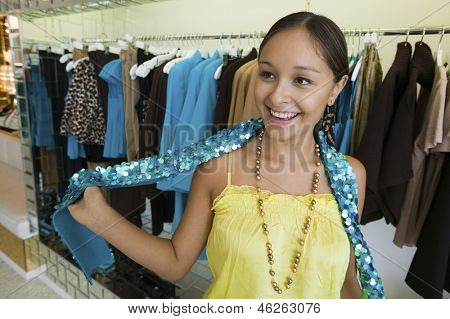 Happy young woman trying on sequin boa in a clothing store
