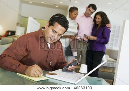 Man adding figures with calculator and laptop with salesperson and couple in background at furniture store