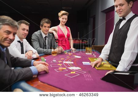 People sitting at blackjack table and smiling in the casino