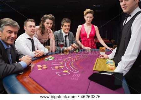 People are sitting at the blackjack  table smiling at the casino