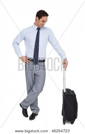 Businessman waiting while holding his luggage on white background