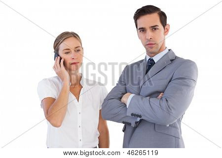 Businesswoman on the phone next to her colleague on white background