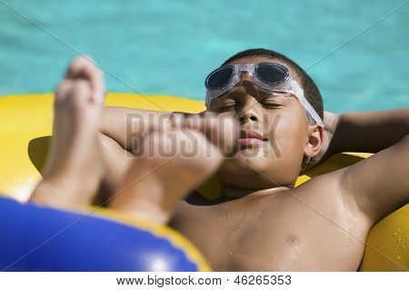 Closeup of a boy relaxing on inflatable raft in the swimming pool