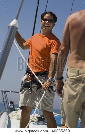 Portrait of a smiling sailor working ropes on a yacht against clear blue sky