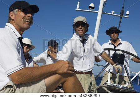 Group of crew members relaxing on yacht deck by helm against clear blue sky