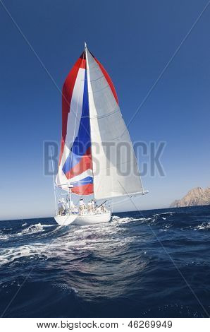 Rear shot of a yacht with colorful sail in the ocean against the clear sky