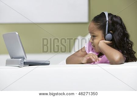 Side view of a little girl lying on sofa and watching movie on portable DVD player