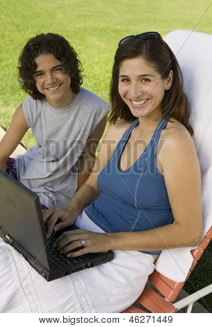 Mother sitting on sunlounger Using Laptop Outdoors with son (13-15) portrait.