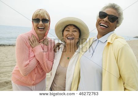 Three cheerful multiethnic female friends laughing on the beach