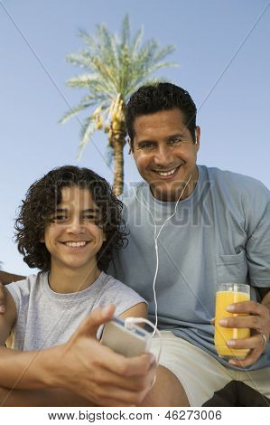 Boy (13-15) holding portable music player father listening with earphones an holding glass of juice front view portrait.