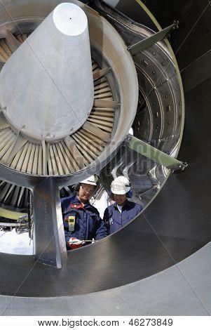 two airplane mechanics standing inside large jumbo jet engine