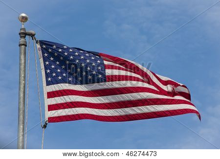 American flag flapping against a blue sky