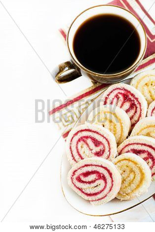 Strawberry and lemon jam swiss roll with cup of coffee