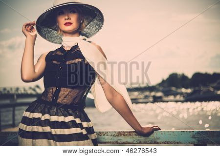 Mujer con sombrero blanco y bufanda de pie cerca de rieles de muelle viejo