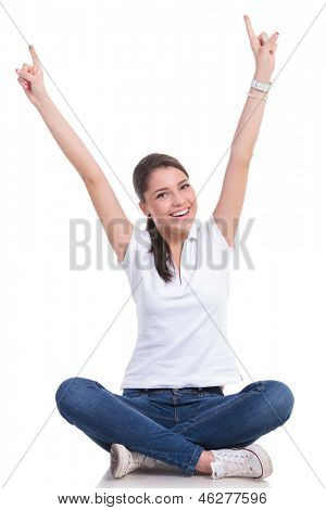 casual young woman sitting with legs crossed cheering with both hands pointing up while smiling to the camera. isolated on white background