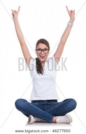 casual young woman sitting with legs crossed and cheering with both index fingers pointing up while smiling to the camera. isolated on white background