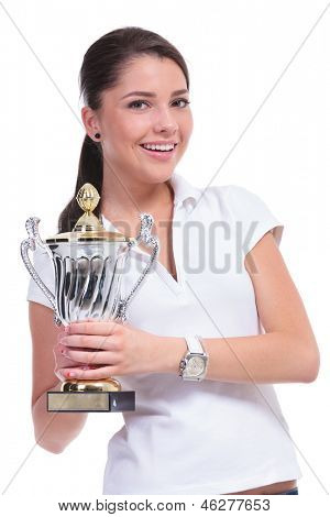 casual young woman presenting a trophy while smiling to the camera . isolated on white background