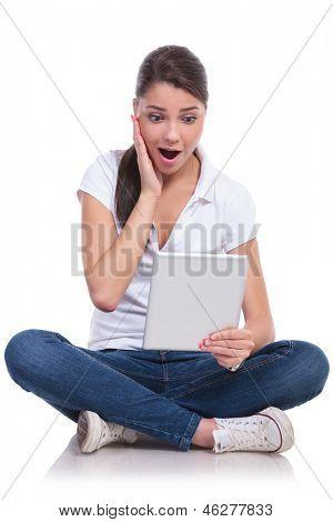 casual mujer joven sentada con las piernas cruzadas y mirando sorprendido en su tablet. aislado en blanco ba