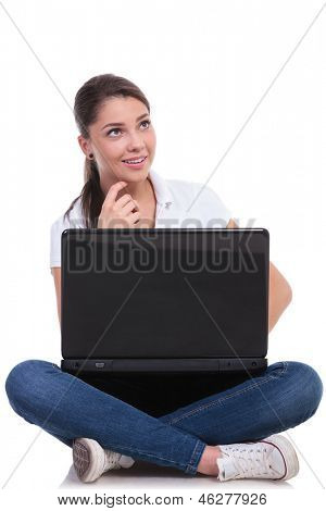 casual young woman sitting with legs crossed and thinking while holding her laptop, looking up and touching her chin. isolated on white background