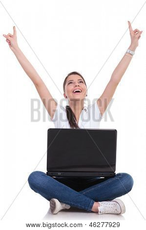 casual young woman sitting with legs crossed, looking up and cheering while holding her laptop. isolated on white background
