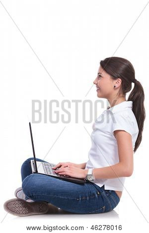 side view of a casual young woman sitting with legs crossed and holding a laptop while looking up and smiling. isolated on white background