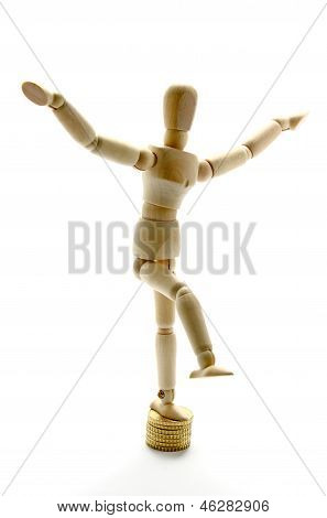 Wooden Mannequin Balancing Over Coins