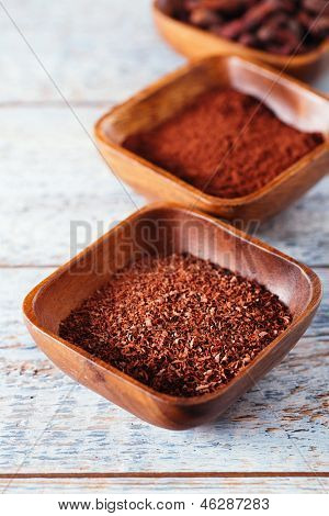 grated chocolate , cocoa beans, powder  in wooden bowls, white wood backdrop