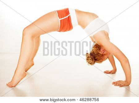 Fit supple woman in sportswear arching over her back so that her toes and the pallams of her hands are touching the floor in a health amd fitness concept on a white background