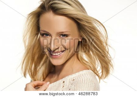 Vivacious blond woman with a lovely warm smile looking at the camera, closeup head and shoulders portrait on white