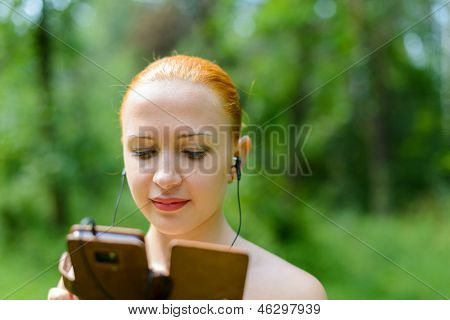 Attractive young woman listening to music with mp3 player and earphone