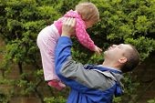 image of kiddy  - Father lifting her daughter up in the air - JPG