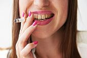 stock photo of addiction to smoking  - smiley woman with yellow dirty teeth holding cigarette - JPG