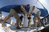 stock photo of work crew  - Low angle view of crew members operating windlass on yacht - JPG