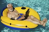 stock photo of recliner  - Portrait of a happy senior man lying on inflatable raft using laptop in swimming pool - JPG