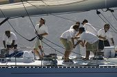 Side view of crew members working on sailboat
