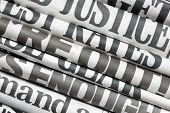 stock photo of newspaper  - Newspaper headlines side on in a stack of daily newspapers - JPG