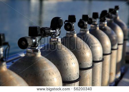 Row of compressed air tanks like they are used during a diving trip.