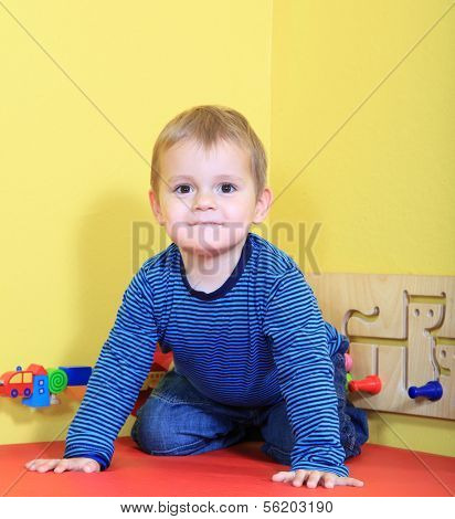 Cute caucasian toddler having fun in kindergarten.