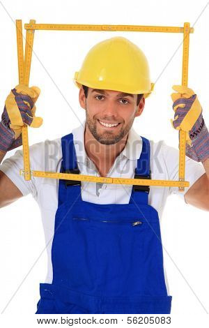 Clumsy construction worker looking through folding rule. All on white background.