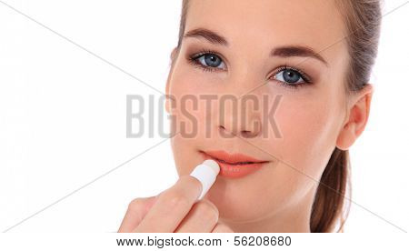 Attractive young woman using lip balm. All on white background.