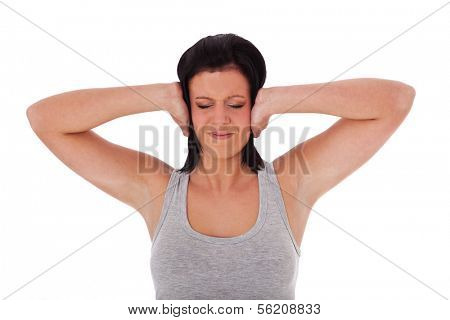 Young woman keeps her ears shut. All on white background.