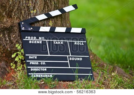 Clapperboard standing at tree trunk