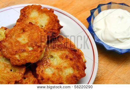 potato pancakes on plate with sour cream