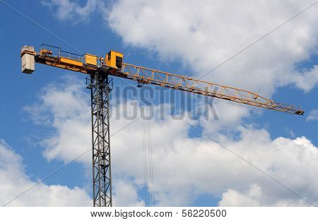 lifting crane under blue sky with clouds