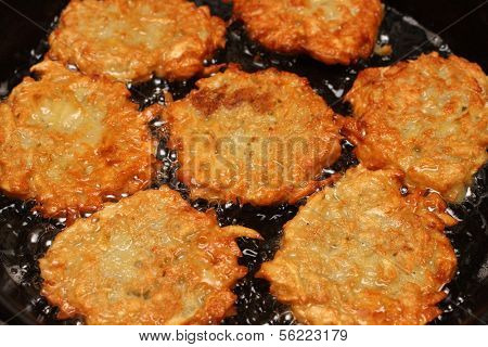 potato pancakes frizzle in black frying pan